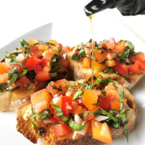 pouring oil on completed bruschetta recipe