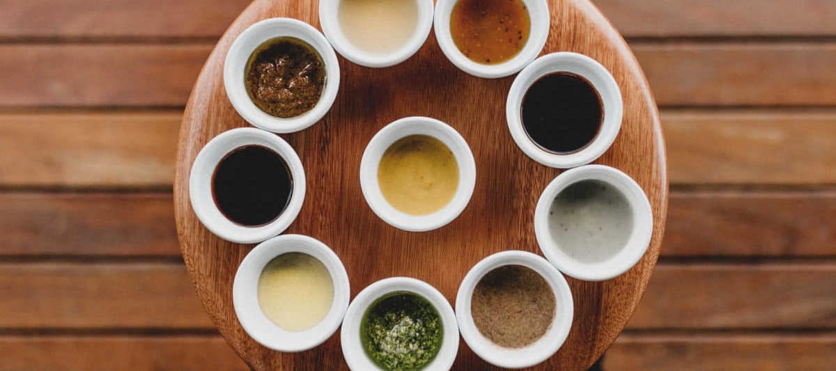 a plate of dips and sauces on a wooden table