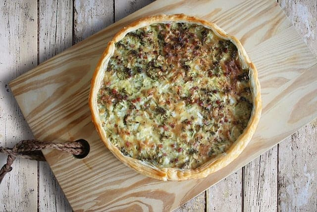 Cooked quiche served on a wooden board
