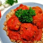 Gluten free meatballs served on a bed of quinoa and garnished with parsley