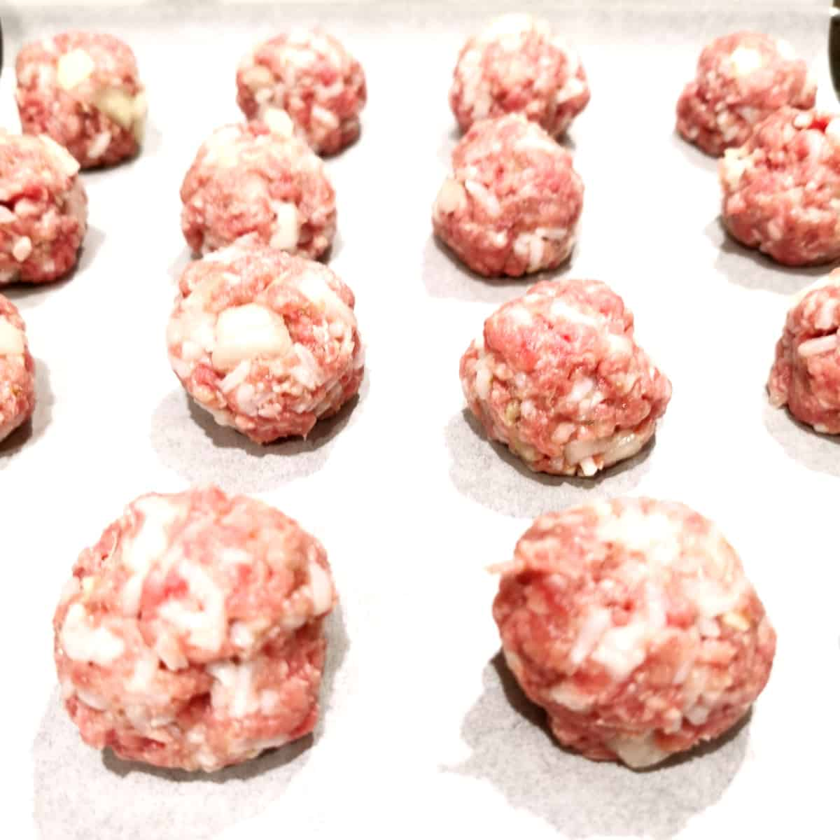 Meatballs rolled and on tray reading for baking