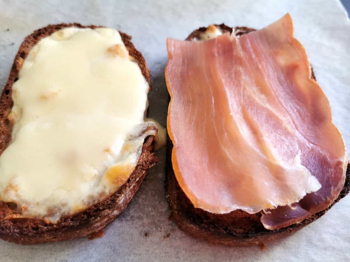 Bread topped with the melted mozzarella and prosciutto