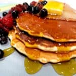 Three pancakes covered in maple syrup, butter and served with berries