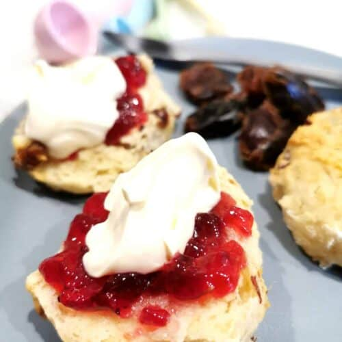 Date scones served on a plate and topped with raspberry jam and cream