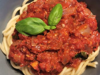 The pasta sauce is served in a bowl on top of gluten free spaghetti with fresh basil leaves