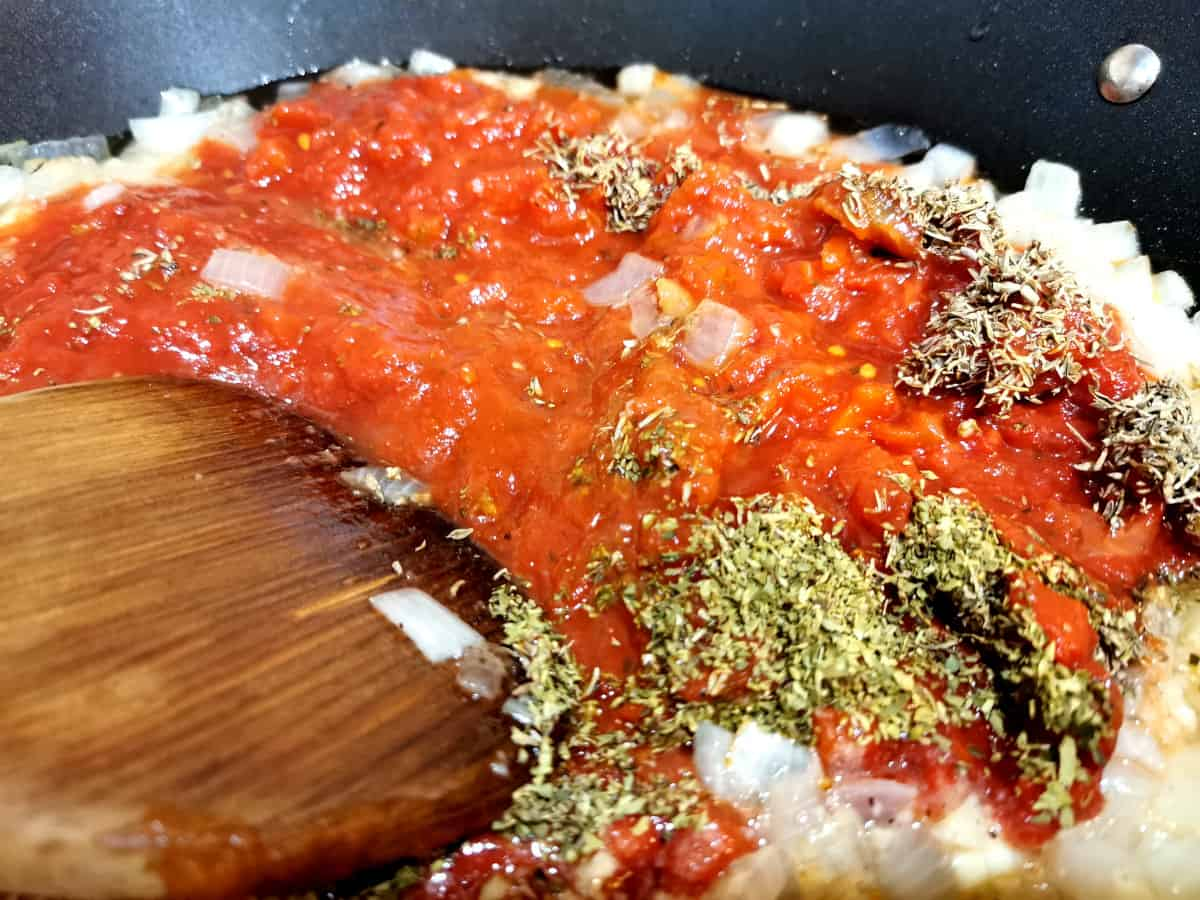 Dried herbs added to frying pan and mixed with spatula