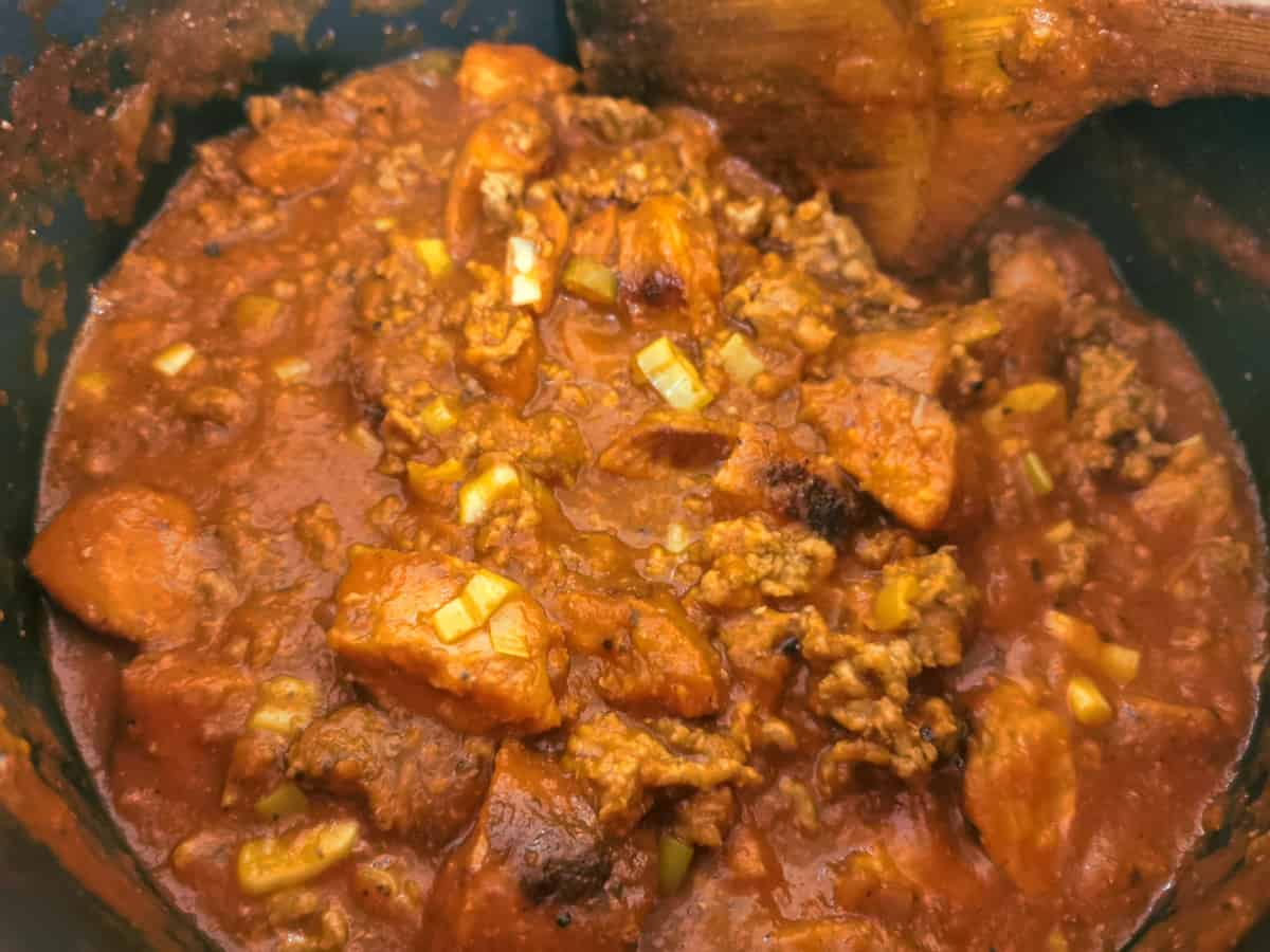 Chopped saugages, ground beef and sauce cooking in a pot