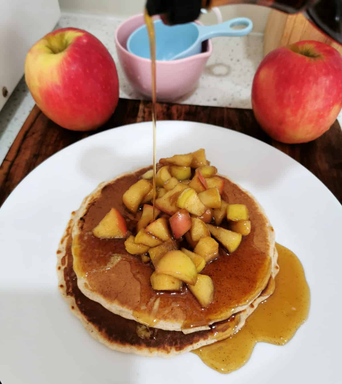 maple syrup being poured onto the apple cinnamon pancakes