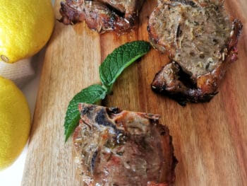 Cooked lamb chops served on a wooden board
